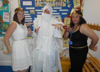 Two women dressed as Ancient Egyptians either side of a man dressed as a mummy.